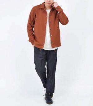 オレンジのコーチジャケット×黒のテーパードパンツ